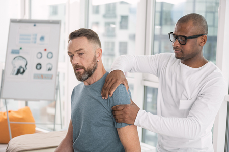 Physical therapy. Smart nice man touching his patients shoulder while doing the therapy Standard-Bild - 99741179