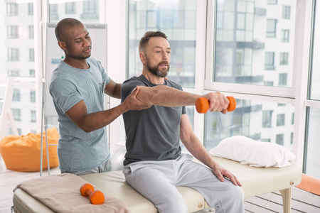 Medical therapist. Pleasant nice doctor standing behind his patient while helping him to raise a hand with a dumbbell