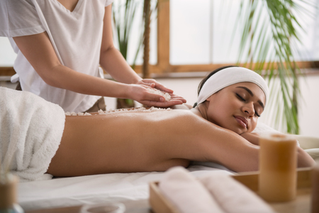 Absolutely peaceful. Peaceful young woman feeling relaxed while enjoying the massage Stock Photo