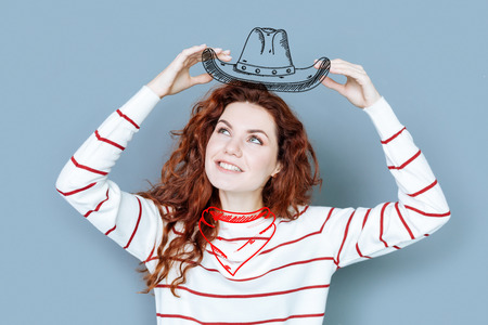 Cowboy costume. Young cheerful woman pretending to be a cowboy while enjoying a funny costume party Stock Photo