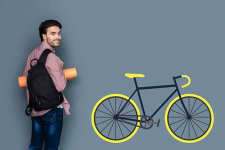 Eco transport. Cheerful enthusiastic young man leading an active lifestyle and choosing a bike while being eco friendly Stock Photo