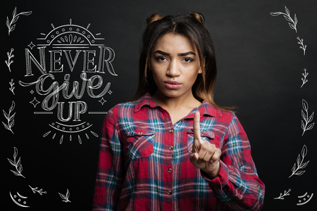 Be confident. Clever professional serious psychologist looking confident while putting one finger up and teaching her clients not to give up Фото со стока