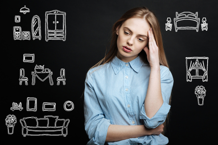 Difficult decision. Serious young student thoughtfully leaning her head on her hand while making a difficult decision about renting a flat Stock Photo