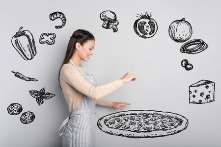 Giant pizza. Cheerful enthusiastic student looking concentrated while making a big delicious pizza