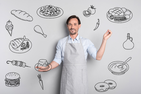 Experienced cook. Cheerful qualified talented cook standing with a tasty pudding in his hands and smiling happily