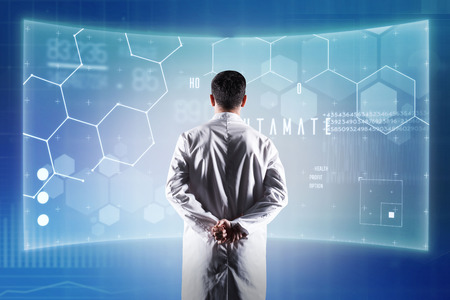 Progressive doctor. Calm progressive doctor looking at the futuristic device while working in his modern laboratory Banque d'images