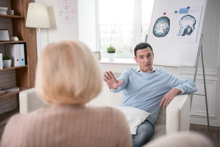 Worried tense man man stretching hand while posing on sofa Foto de archivo