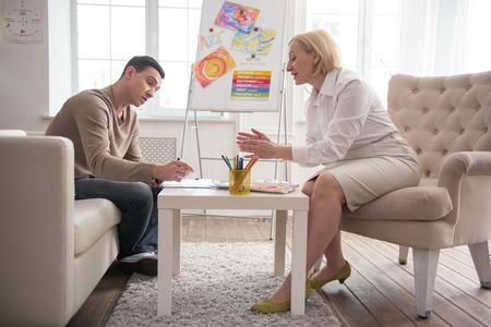 Art and psychotherapy. Focused man visiting jovial psychologist while trying art therapy Stock Photo
