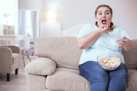 Little pleasures. Plump young woman opening her mouth while throwing in it a handful of popcorn