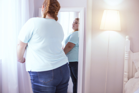 Mirror on the wall. Stout young woman standing next to mirror while admiring herself