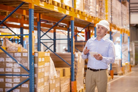 Safety measures. Serious adult man wearing helmet while checking the equipment in the warehouse