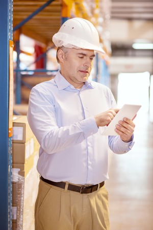Industrial business. Serious professional businessman wearing a helmet while working in his warehouse Stock Photo