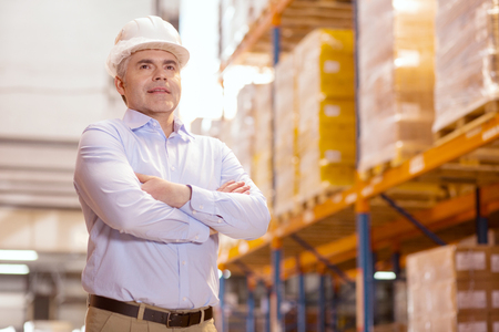 Business owner. Smart confident man wearing a helmet while being in his warehouse