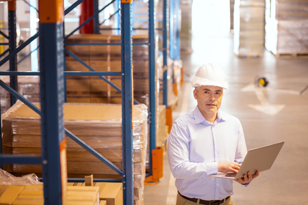 Product sales. Pleasant smart businessman visiting his warehouse while working with the wholesale market Stock Photo
