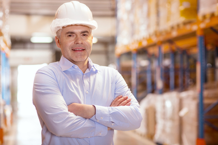 Professional occupation. Confident smart businessman smiling while working in his warehouse