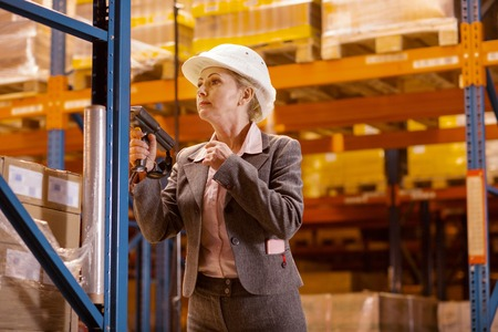Safety rules. Serious pleasant woman wearing a helmet while adhering to the safety rules in the warehouse