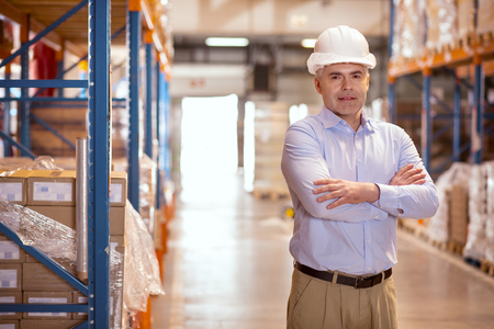 Successful business. Confident nice businessman looking at you while being in the warehouse Stock Photo