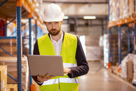Logistics manager. Serious bearded man looking at you while working as a logistics manager in the warehouse Stock Photo
