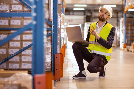 Gerente de inventario. Buen hombre inteligente sosteniendo una computadora portátil y contando cajas en el almacén