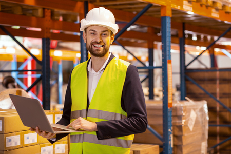 Logistics system. Happy cheerful man looking at you while organizing the logistics system of the warehouse
