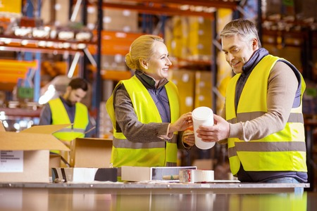 Professional cooperation. Positive nice people helping each other while working together in the warehouse Stock Photo