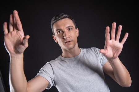 Virtual technology. Pleasant nice confident man standing against black background and pressing the screen while using virtual technology