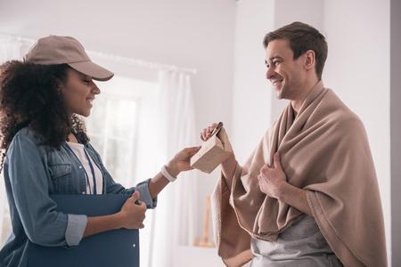 Gracias. Hombre positivo alegre mirando a la persona de entrega mientras toma su paquete