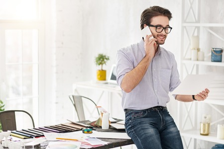 Good day. Attractive happy man talking on the phone and holding a sheet of paper Stock Photo