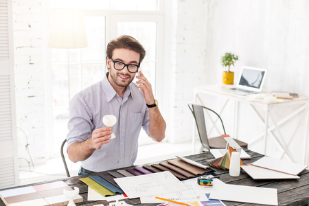 My working day. Joyful dark-haired man talking on the phone and holding a white object Stock Photo