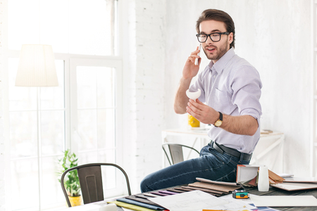 Nice talk. Alert bearded man talking on the phone while sitting on the table Stock Photo