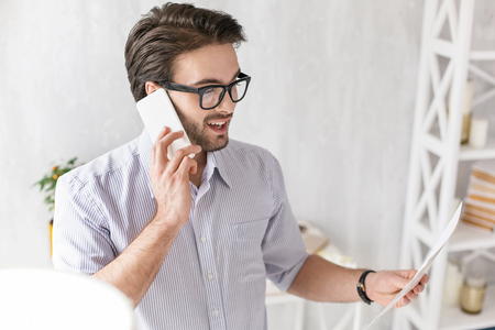 Success. Cheerful young manager talking on the phone and holding a sheet of paper Stock Photo