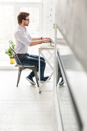 Working day. Serious bearded man sitting at the table and working on his laptop Stock Photo
