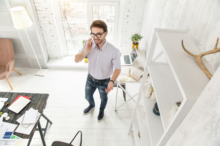 Doing business. Cheerful young businessman talking on the phone while standing in the office