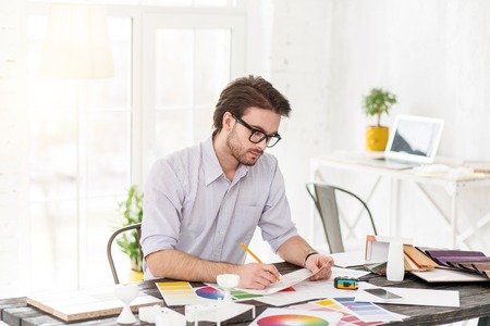 My favourite work. Attractive concentrated man sitting at the table and holding a sheet of paper and a pencil Stock Photo