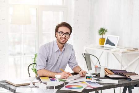 My inspiration. Good-looking delighted man sitting at the table and holding a sheet of paper and a pencil Stock Photo