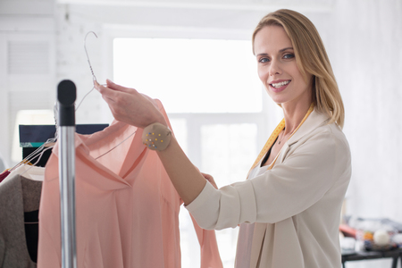Women in fashion. Positive jovial businesswoman putting garment on stand while looking at camera