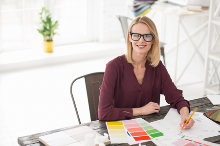 Not sure. Ambitious female designer sitting at table while using pencil Stock Photo