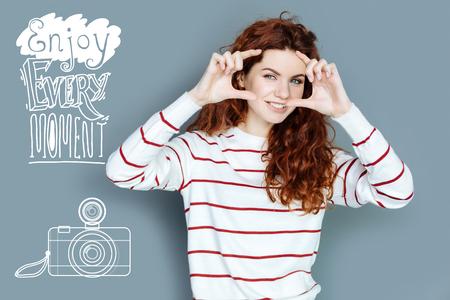Taking photos. Cheerful young emotional tourist enjoying her holidays and taking photos Standard-Bild - 100837562