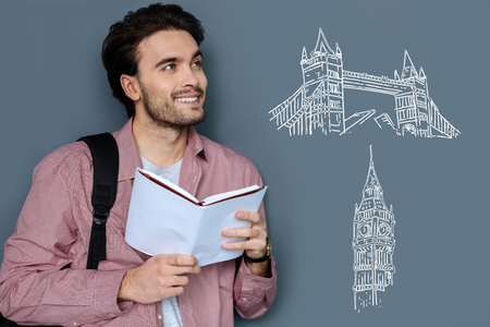 Pleasant dreams. Cheerful dreamy student standing with a book in his hands and thinking about travelling abroad Stock Photo - 100837598