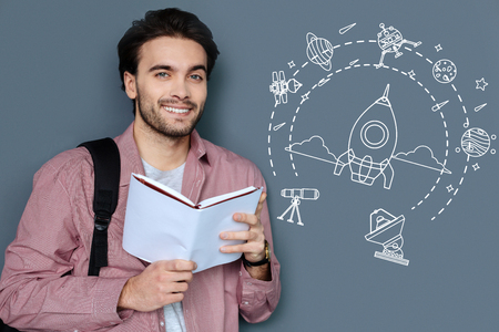 Ambitious person. Cheerful enthusiastic student dreaming about flying into the open space while standing with a book in his hands