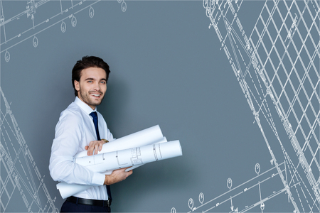 Holding graphics. Emotional young architect looking elegant while standing with his graphics and waiting for the colleagues