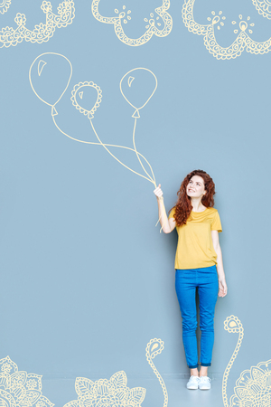 Lovely balloons. Positive kind attentive mother carrying lovely balloons while preparing a surprise for her children