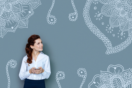 Switching attention. Waist up of young gorgeous business woman with curly hair looking away and using a mobile phone while standing against well designed grey background