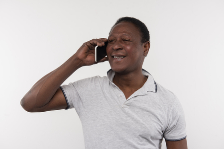 Pleasant communication. Joyful nice man putting his phone to the ear while talking on the phone Stock Photo