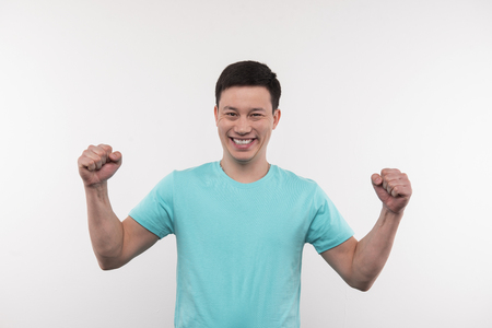 Personal success. Joyful young man holing his hands up while thinking about his personal success Stock Photo