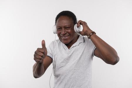 Great music. Joyful happy man showing OK gesture while enjoying the music