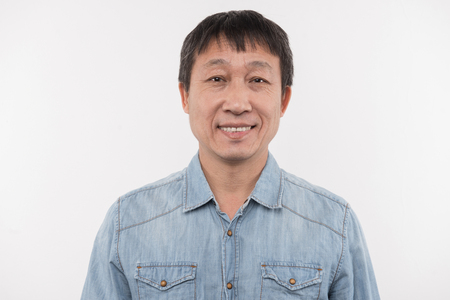 Ethnic nationality. Portrait of a nice Asian man smiling while looking at you