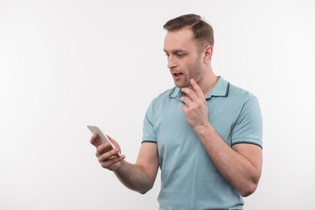 Online communication. Nice pleasant man holding his phone while checking messages