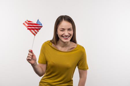 American citizen. Joyful nice woman holing the US flag while expressing her patriotic feelings