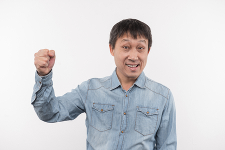 Great mood. Pleasant delighted man smiling while holding his fist up Stock fotó